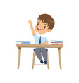 cute boy sitting at the desk and rising his hand vector image