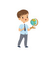 cute boy standing with globe at geography lesson vector image vector image