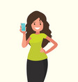 a smiling young woman holds smartphone in her vector image