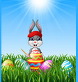 easter bunny painting easter eggs in the grass bac vector image