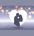 silhouette of a kissing couple in a heart vector image