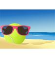 Tennis ball on the beach sand vector image