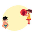 two kids playing on sandy beach with ball bucket vector image vector image