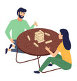 couple plays in jenga tower sitting at round vector image