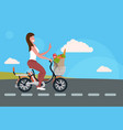 woman cycling bicycle carrying paper bag with food vector image