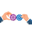 businessman hands joining two gears together vector image