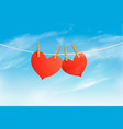 two hearts hanging on a rope in front a sky vector image vector image