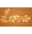Christmas light on love sign with wooden backgroun vector image