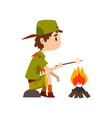 boy scout character in uniform frying marshmallow vector image