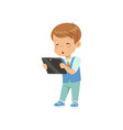 cute little boy standing with a tablet pc vector image vector image