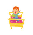 cute red-haired boy waking up in bed and yawning vector image