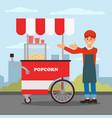 friendly seller standing near popcorn cart street vector image