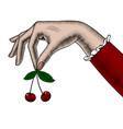 womans hand holding cherries in her fingers vector image