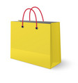 ywllow paper shopping bag with red rope handles vector image vector image