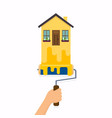 hand holding roller brush and painting a house vector image