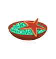 ceramic bowl with green salt and marine starfish vector image vector image