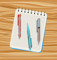 notebook orange pen blue pen vector image