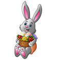 cartoon easter bunny holding a basket full of eggs vector image vector image