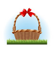 empty basket with a red bow standing on the grass vector image vector image