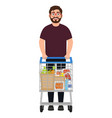 A bearded man stands with a shopping trolley the