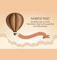hot air balloon with ribbon in the sky with clouds vector image