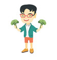 little asian boy laughing and holding broccoli vector image