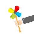 businessman hand holding paper windmill pinwheel vector image vector image