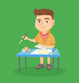caucasian boy drawing a picture with a paint brush vector image vector image