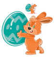easter bunny holding a decorated egg in its vector image vector image