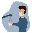 man in a protective mask washes his hands vector image vector image