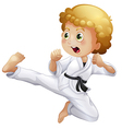 A cute little boy doing karate vector image vector image