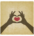 hands in heart shape on vintage background vector image vector image