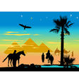 travelers around the pyramids and palm trees at