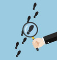hand holding magnifying glass over footsteps vector image