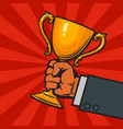 businessman hand holding winners gold cup trophy vector image