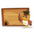 An owl wearing a graduation cap beside a wooden vector image vector image