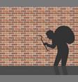 burglar in front of brick wall vector image