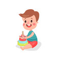 cute little boy playing colorful pyramid toy vector image