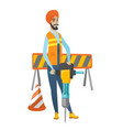 young hindu builder using pneumatic hammer