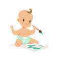 happy baby in a diaper painting with paintbrush vector image vector image
