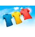 three t-shirts hanging on rope against blue sky vector image vector image