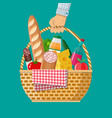 hand holds wicker picnic basket full of products vector image vector image