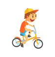 funny little boy in yellow baseball cap riding vector image