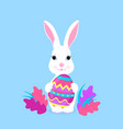cute easter bunny holds paschal egg in its paws vector image