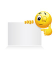 smiley emoticon holding and showing advertise vector image vector image