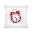 Red retro alarm clock on white pillow
