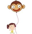 A little girl holding a monkey balloon