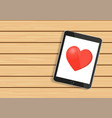 tablet mobile isolated with red heart on wooden vector image
