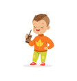 cute little boy in warm clothing standing with cup vector image vector image