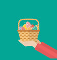 hand holding basket with easter eggs vector image vector image